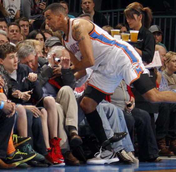Oklahoma City Thunder shooting guard Thabo Sefolosha (2) falls into the fans while going for a loose ball during the NBA basketball game between the Oklahoma City Thunder and the Los Angeles Clippers at Chesapeake Energy Arena on Wednesday, March 21, 2012 in Oklahoma City, Okla.  Photo by Chris Landsberger, The Oklahoman