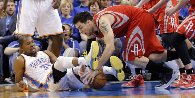 Oklahoma City's Kevin Durant (35) battles for a loose ball with Houston's Carlos Delfino (10) during Game 2 in the first round of the NBA playoffs between the Oklahoma City Thunder and the Houston Rockets at Chesapeake Energy Arena in Oklahoma City, Wednesday, April 24, 2013. Photo by Chris Landsberger, The Oklahoman