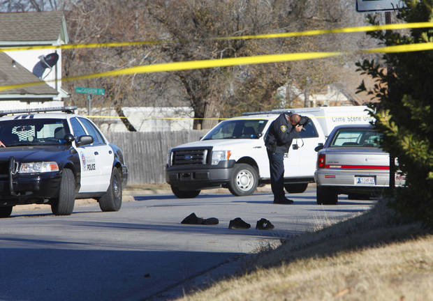 A law enforcement officer takes photographs Tuesday at the scene of a police officer-involved shooting at the corner of Cashion Place and N Youngs Boulevard in Oklahoma City. In the road are the shoes and clothing of the deceased suspect. Photo By David McDaniel, The Oklahoman