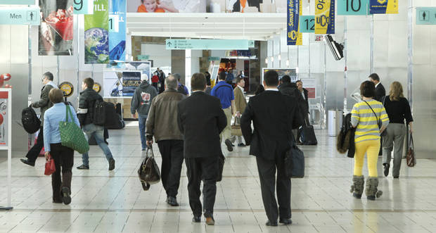 Holiday travelers walk through the terminal at Will Rogers World Airport in Oklahoma City on Tuesday. An estimated 80,000 passengers will pass through the airport this week as Christmas nears. Photos by PAUL HELLSTERN, The Oklahoman