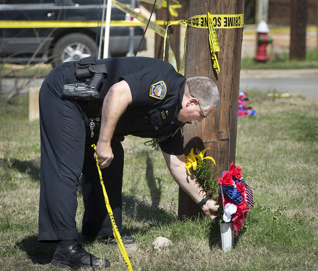 Bryan Police Officer Al Wescoat straightens flowers at a makeshift memorial near a Knights of Columbus Hall, Saturday, Feb. 16, 2013, in Bryan, Texas. Two Texas fire lieutenants have died of burns after battling a lodge hall fire, and two are hospitalized, a city official said Saturday. (AP Photo/Bryan College Station Eagle, Stuart Villanueva)