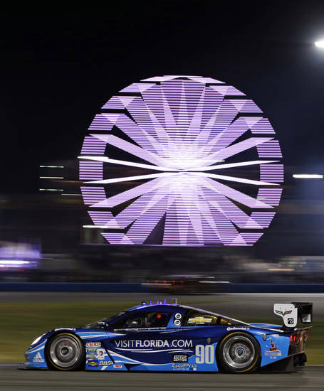 Antonio Garcia, of Spain, drives the Spirit of Daytona Racing Corvette DP past the infield midway during the Grand-Am Series Rolex 24 hour auto race at Daytona International Speedway, Saturday, Jan. 26, 2013, in Daytona Beach, Fla. (AP Photo/John Raoux)