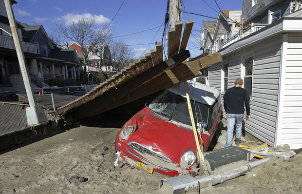 In this Nov. 3, photo, a man passes walks by a piece of the Rockaways boardwalk that was washed into Beach 91st Street, alongside a small car that was destroyed by Superstorm Sandy earlier in the week, in the Rockaways neighborhood in New York. AP Photo <strong>Kathy Willens - AP</strong>