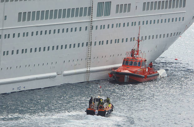 An orange rescue boat docks by a capsized lifeboat, obscured behind, from the British-operated cruise ship Thomson Majesty in Santa Cruz port of the Canary Island of La Palma, Spain, Sunday Feb. 10, 2013. A lifeboat from the Thomson Majesty fell into the sea at port in Spain�s Canary Islands, killing five people and injuring three others Sunday, officials said. Rescue personnel were called to the dockside after a lifeboat with occupants had fallen overboard from a cruise ship. Spanish national broadcaster RTVE said an emergency training drill was taking place at the time of the accident. (AP Photo/Manuel Gonzalez)