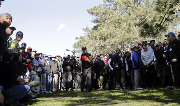 Tiger Woods, center, watches his second shot land on the fairway from out of bounds during the fourth round of the Farmers Insurance Open golf tournament at the Torrey Pines Golf Course, Monday, Jan. 28, 2013, in San Diego. (AP Photo/Lenny Ignelzi)