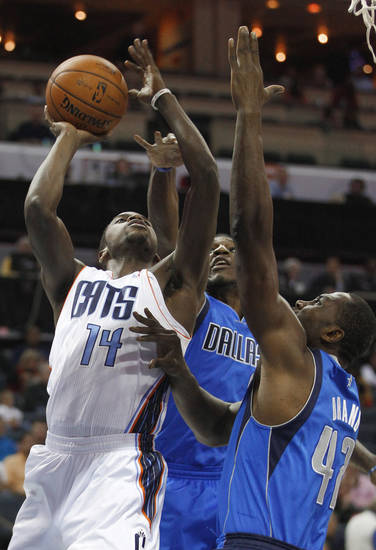 Charlotte Bobcats' Michael Kidd-Gilchrist (14) tries to shoot over Dallas Mavericks' Elton Brand (42) and Jae Crowder, back, during the first half of an NBA basketball game in Charlotte, N.C., Saturday, Nov. 10, 2012. (AP Photo/Chuck Burton)