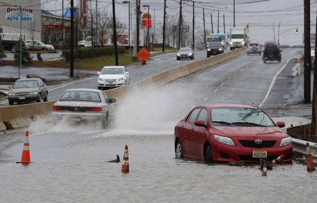 A vehicle stands abandoned facing in the wrong direction as traffic flows around  floodwaters on Route 35 in Keyport, N.J., where an overnight storm caused coastal flooding, Thursday, Dec. 27, 2012. (AP Photo/Julio Cortez)