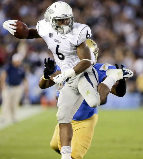 Nevada running back Don Jackson runs past UCLA defensive end Keenan Graham during the first half of an NCAA college football game in Pasadena, Calif., Saturday, Aug. 31, 2013. (AP Photo/Chris Carlson)
