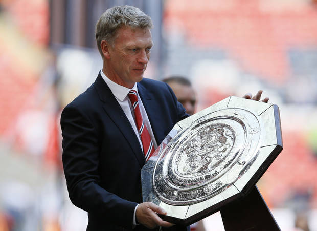 Manchester United's manager David Moyes holds the trophy after their win against Wigan Athletic at the end of their English FA Community Shield soccer match at Wembley Stadium in London, Sunday, Aug. 11, 2013. (AP Photo/Kirsty Wigglesworth)