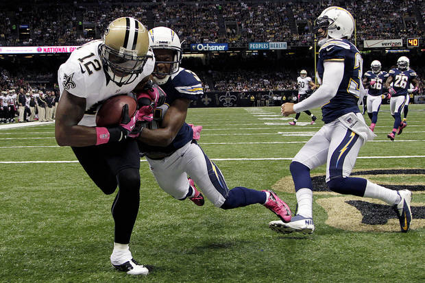 New Orleans Saints wide receiver Marques Colston (12) pulls in a touchdown pass in front of San Diego Chargers cornerback Marcus Gilchrist (38) in the first half of an NFL football game at Mercedes-Benz Superdome in New Orleans, Sunday, Oct. 7, 2012. (AP Photo/Bill Haber)