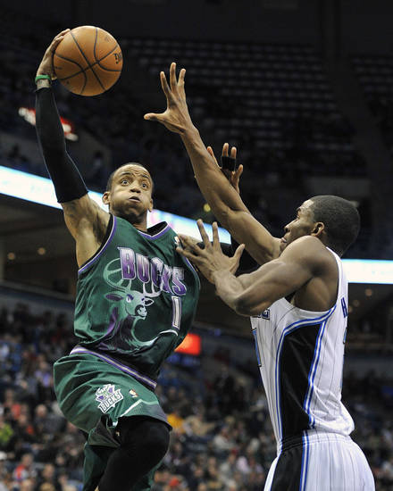 Milwaukee Bucks' Monta Ellis, left, drives to the basket over Orlando Magic's Moe Harkless during the second half of an NBA basketball game on Saturday, Feb. 2, 2013, in Milwaukee. (AP Photo/Jim Prisching)