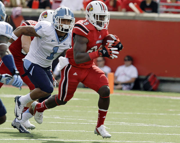 Louisville running back Jeremy Wright (28) runs ahead of North Carolina defender Gene Robinson (1) during the first half of an NCAA college football game in Louisville, Ky., Saturday, Sept. 15, 2012. (AP Photo/Garry Jones)