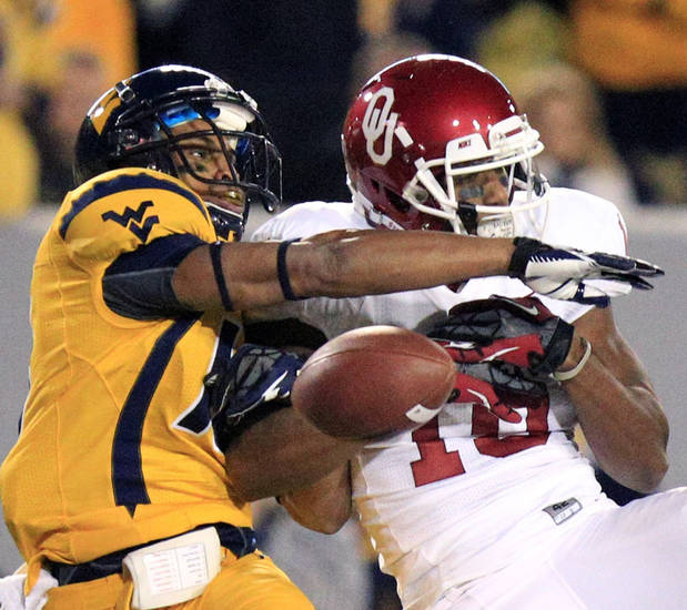 West Virginia's Terrell Chestnut (16) breaks up a pass intended for Oklahoma's Jaz Reynolds (16) during the first quarter of their NCAA college football game against Oklahoma in Morgantown, W.Va., on Saturday, Nov. 17, 2012. (AP Photo/Christopher Jackson)