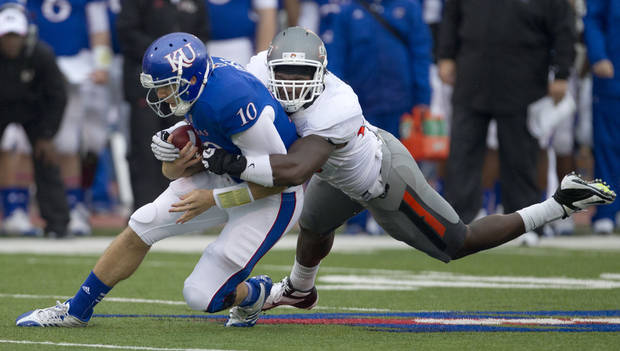 Kansas quarterback Dayne Crist (10) is tackled by Oklahoma State defensive tackle Nigel Nicholas (89) during the first half of an NCAA college football game in Lawrence, Kan., Saturday, Oct. 13, 2012. (AP Photo/Orlin Wagner)