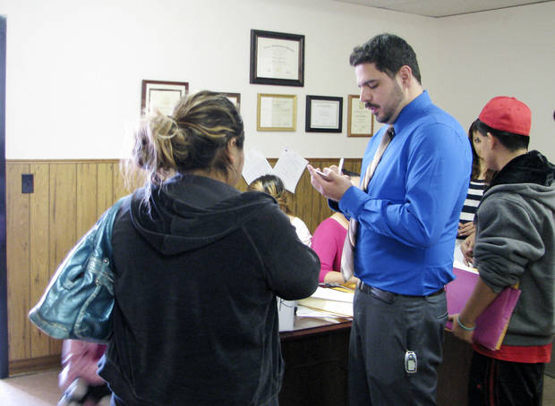 Fredy Valencia writes down the name and information of a woman who walked in seeking information about Deferred Action for Childhood Arrivals, a federal program that provides some undocumented immigrants relief from deportation. Valencia was working at a clinic on Oct. 27 at Capitol Hill Community Center.
