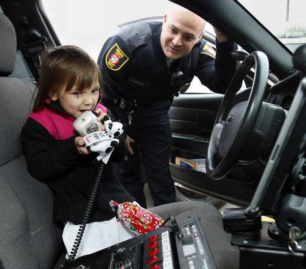 Kaelynn Fenimore, 5, uses the outside speaker of Moore Police officer Trevor Troxell's police car before her ride to the store during the Second Annual Shop with a Cop on Saturday, Dec. 8, 2012 in Moore, Okla. Photo by Steve Sisney, The Oklahoman