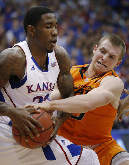 Kansas forward Jamari Traylor (31) keeps the ball away from Oklahoma State guard Phil Forte (13) during the first half of an NCAA college basketball game in Lawrence, Kan., Saturday, Feb. 2, 2013. (AP Photo/Orlin Wagner) ORG XMIT: KSOW104