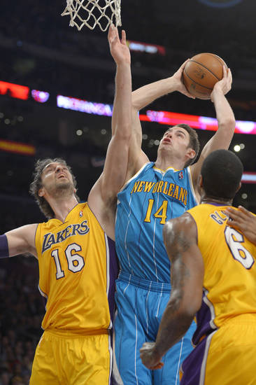 New Orleans Hornets forward Jason Smith, center, puts up a shot as Los Angeles Lakers forwards Pau Gasol, left, of Spain, and Earl Clark defend during the first half of an NBA basketball game, Tuesday, Jan. 29, 2013, in Los Angeles. (AP Photo/Mark J. Terrill)