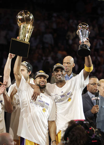 FILE - In this June 17, 2010, file photo, Los Angeles Lakers guard Derek Fisher, left, holds the Larry O'Brien trophy and guard Kobe Bryant holds the most valuable player trophy after winning the NBA basketball championship against the Boston Celtics in Los Angeles. The Lakers shook up their roster at the trade deadline by dealing away Fisher, their starting point guard and a five-time NBA champion in Los Angeles alongside Kobe Bryant. (AP Photo/Jae C. Hong, File)