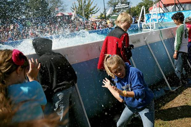 Breanna Jay, age 10, and other children, react to getting splashed by water as dogs jump into a pool during a performance at the Oklahoma State Fair in Oklahoma City, Sept. 26, 2010. Photo by John Clanton, The Oklahoman ORG XMIT: KOD