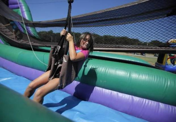 Bryanna McAlvain, 9, of Seminole, takes a ride on a zip-line at a Fourth of July Celebration in Seminole, Okla., July 4, 2012. Photo by Garett Fisbeck, The Oklahoman