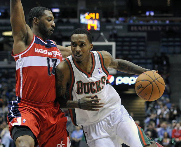 Washington Wizards' A.J. Price (12) defends as the Milwaukee Bucks' Brandon Jennings drives to the basket during the second half of an NBA basketball game Monday, Feb. 11, 2013, in Milwaukee. The Wizards defeated the Bucks 102-90. (AP Photo/Jim Prisching)