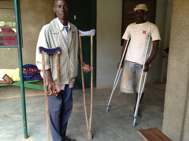 A man from the Ivory Coast, whose leg was amputated after a motorcycle accident, receives new crutches from a representative of 1040i.