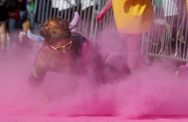 A competitor rolls across the finish line  the Color Me Rad 5K at the State Fair Park in Oklahoma City, Saturday, July 14, 2012. The race helped raised money for the Cystic Fibrosis Foundation. Photo by Sarah Phipps, The Oklahoman.