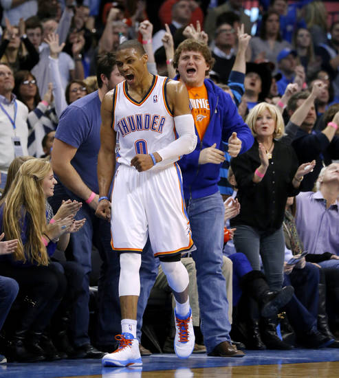 Oklahoma City guard Russell Westbrook reacts after a basket during the Thunder's 111-105 win over the Dallas Mavericks on Thursday. OU offensive guard Bronson Irwin, right, and center Gabe Ikard, who is behind Westbrook, are cheering the Thunder on. PHOTO BY BRYAN TERRY, THE OKLAHOMAN