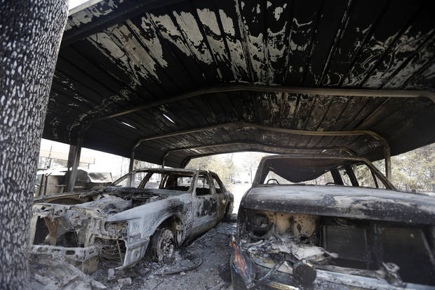 Burned cars are pictured , Sunday, Aug. 5, 2012, in the community of Oak Grove near Drumright, Okla., after wildfires moved through the area Saturday. Photo by Sarah Phipps, The Oklahoman