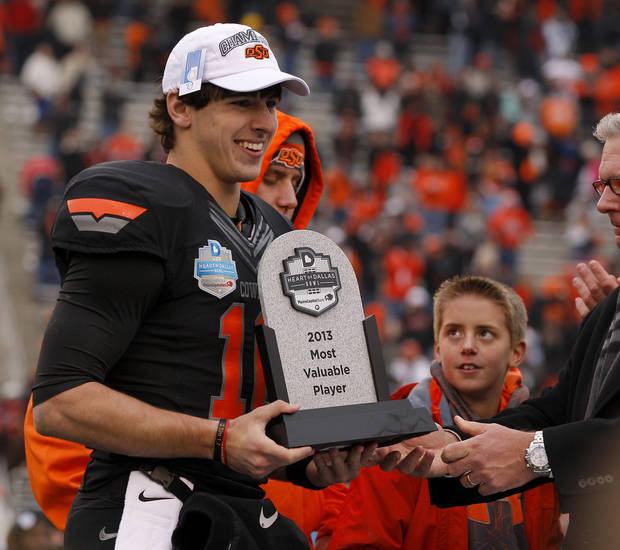 Oklahoma State&#039;s Clint Chelf  receives  the Most Valuable Player award after the Heart of Dallas Bowl football game between Oklahoma State University and Purdue University at the Cotton Bowl in Dallas, Tuesday, Jan. 1, 2013. Oklahoma State won 58-14. Photo by Bryan Terry, The Oklahoman