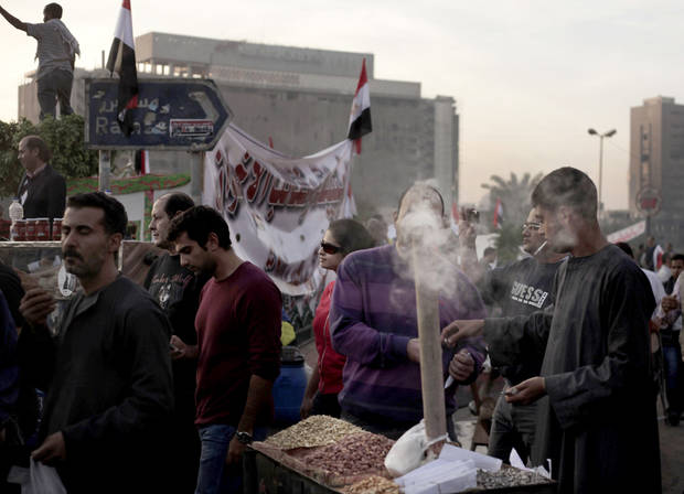 An Egyptian street vendor sells nuts during a demonstration in Tahrir Square in Cairo, Egypt, Friday, Nov. 30, 2012. Liberal and secular parties held major protests against Egyptian President Mohammed Morsi's latest decrees granting himself almost complete powers. (AP Photo/Nariman El-Mofty)