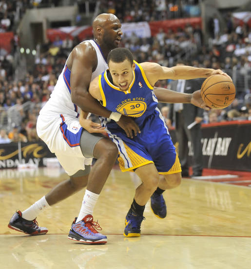 Los Angeles Clippers forward Lamar Odom, left, defends as Golden State Warriors guard Stephen Curry (30) drives to the basket in the first half of an NBA basketball game in Los Angeles on Saturday, Nov. 3, 2012. (AP Photo/Richard Hartog) ,
