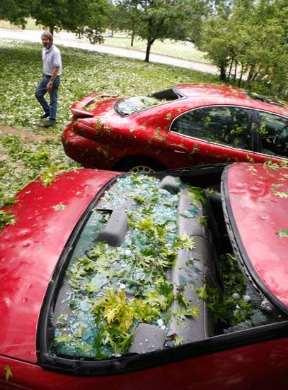 Nichols Hills resident Tommy Dumbell looks at his two cars which had their windows knocked out by up tennis ball-size hail after a severe thunderstorm moved through Nichols Hills and NW Oklahoma City , Sunday, May 16, 2010. By Paul Hellstern, The Oklahoman