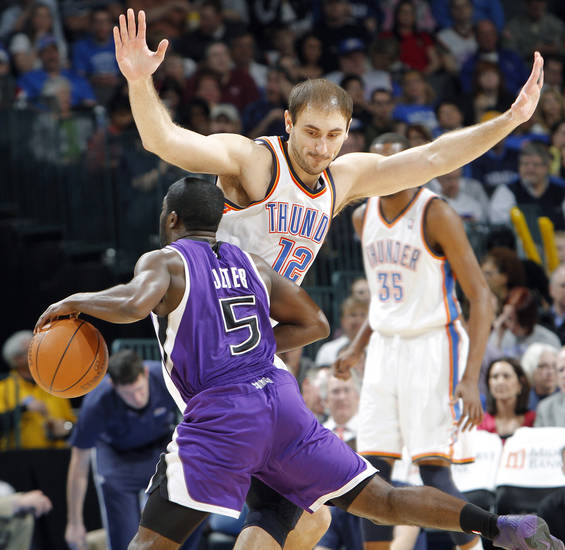The Thunder's Nenad Krstic (12) defends on the Kings' Eugene Jeter (5) during the NBA basketball game between the Oklahoma City Thunder and The Sacramento Kings on Tuesday, Feb. 15, 2011, Oklahoma City Okla.  Photo by Chris Landsberger, The Oklahoman