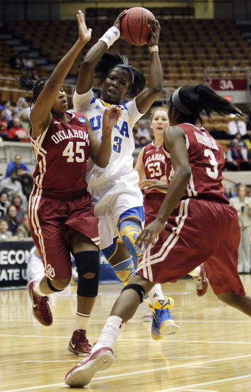 UCLA's Markel Walker, center, drives between Oklahoma's Jasmine Hartman, left, and Aaryn Ellenberg during the first half of a second-round game in the women's NCAA college basketball tournament, Monday, March 25, 2013, in Columbus, Ohio. (AP Photo/Jay LaPrete) ORG XMIT: OHJL103