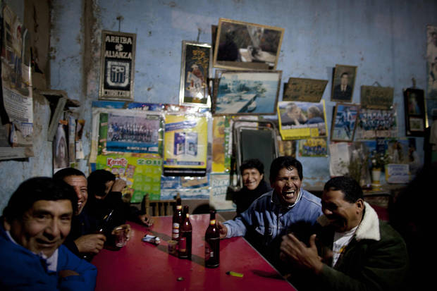 In this Sept. 22, 2012 photo, villagers gather in a bar in La Quebrada, Peru. Every year, Peruvians descended from African slaves come to La Quebrada to celebrate the adored black saint Santa Efigenia, the only African saint venerated in Peru. A chapel was built in La Quebrada in the 18th century dedicated to Santa Efigenia, who was popular among the then Spanish colony's African slaves. Cat races, a fireworks dance and a night of eating and drinking close out the celebration. (AP Photo/Rodrigo Abd)