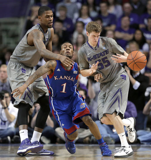 Kansas State forward Jordan Henriquez, left, and guard Will Spradling (55) and Kansas guard Naadir Tharpe (1) vie for a loose ball during the first half of an NCAA college basketball game Tuesday, Jan. 22, 2013, in Manhattan, Kan. (AP Photo/Charlie Riedel)