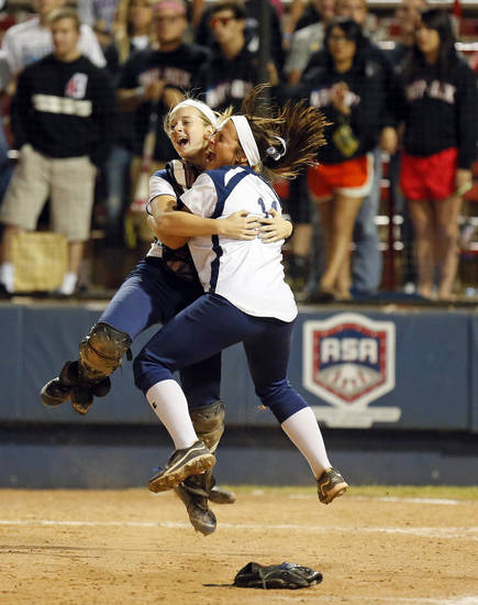 Edmond North's Ashtyn Crouch (24), left, and Jordan Dixon (11) celebrate as Moore fans look on after Edmond North won the 6A state championship fast-pitch softball game against Moore at ASA Hall of Fame Stadium in Oklahoma City, Monday, Oct. 15, 2012. Edmond North won, 11-2. Photo by Nate Billings, The Oklahoman
