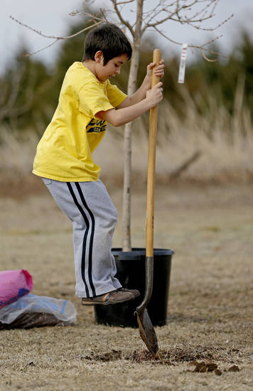 Anthony Pontious, 7, with Cub Scout Pack 91, leaps onto shovel as he digs a hole to plant a tree.
