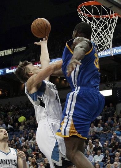 Golden State Warriors' Festus Ezeli, right, of Nigeria, breaks up a shot-attempt by Minnesota Timberwolves' Andrei Kirilenko, of Russia, in the first half of an NBA basketball game on Friday, Nov. 16, 2012, in Minneapolis. (AP Photo/Jim Mone)