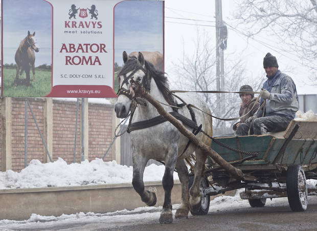 CORRECTS LOCATION In this Feb. 12, 2013  men ride on a horse pulled cart passing by the Doly Com abattoir, in Roma, Romania,  one of the two Romanian plants suspected in the recent European horse meat scandal . Europe�s horsemeat scandal has focused the spotlight on Romania and its network of 35 plants authorized to butcher horses. France says Romanian butchers were part of a supply chain that resulted in horsemeat being labeled as beef in frozen meals across Europe. The Romanians have bristled and say the meat was properly declared when it left the country.  (AP Photo/Vadim Ghirda, File)