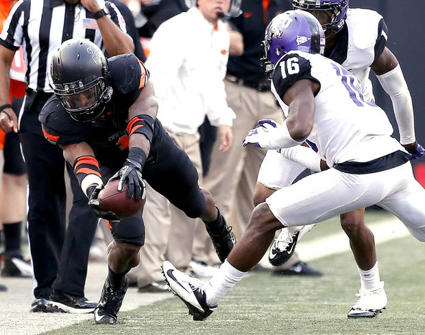 Oklahoma State&#039;s Joseph Randle (1) dives for a first down in front of TCU&#039;s Keivon Gamble (16) during a college football game between Oklahoma State University (OSU) and Texas Christian University (TCU) at Boone Pickens Stadium in Stillwater, Okla., Saturday, Oct. 27, 2012. Photo by Sarah Phipps, The Oklahoman