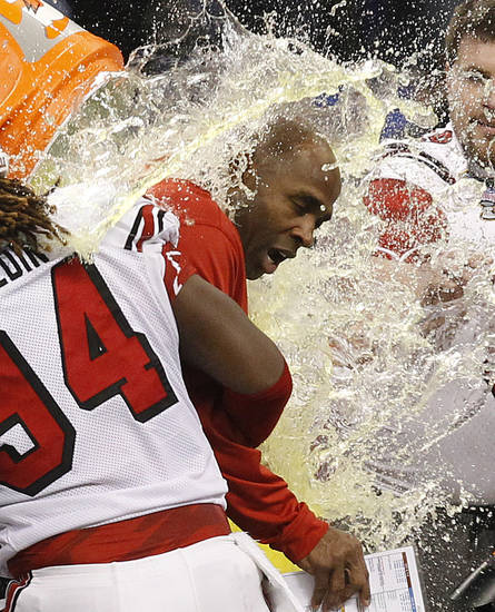 Louisville head coach Charlie Strong is dunked by his team following a 33-23 win over Florida in the Sugar Bowl NCAA college football game Wednesday, Jan. 2, 2013, in New Orleans. (AP Photo/Butch Dill)