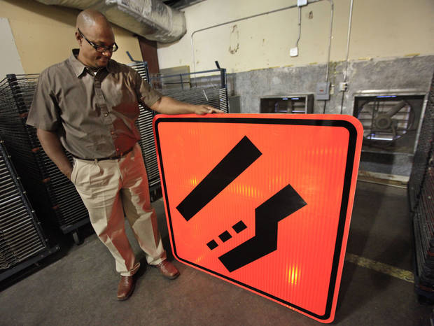 Marco White looks over a freshly screened road sign at the state�s sign shop in Oklahoma City. Photo By David McDaniel, The Oklahoman