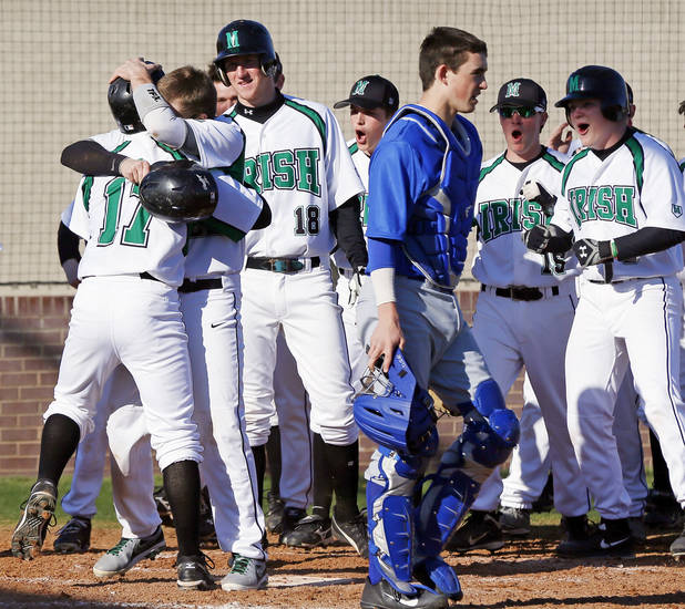 The Bishop McGuinness Irish celebrate a 3-run home run by Thorn Cowley (17) as Deer Creek catcher Alex Forget (15) walks away in the third inning during a high school baseball game at Bishop McGuinness in Oklahoma City, Monday, March 11, 2013. Photo by Nate Billings, The Oklahoman