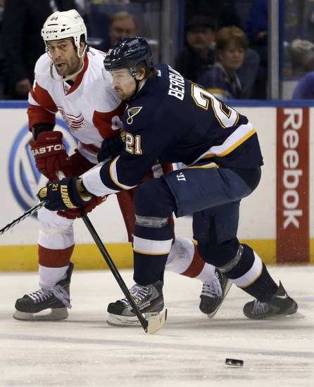 Detroit Red Wings' Todd Bertuzzi, left, passes the puck around St. Louis Blues' Patrik Berglund, of Sweden, during the first period of an NHL hockey game Thursday, Feb. 7, 2013, in St. Louis. (AP Photo/Jeff Roberson)