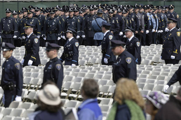 Police officers and civilians arrive to a memorial service for fallen Massachusetts Institute of Technology campus officer Sean Collier at MIT in Cambridge, Mass. Wednesday, April 24, 2013.  Authorities say Collier was killed by the Boston Marathon bombing suspects last Thursday. He had worked for the department a little more than a year.  (AP Photo/Elise Amendola)