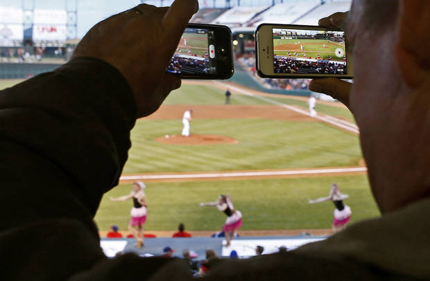 A fan records video with two phones of the between-inning entertainment during the Oklahoma City RedHawks home opener against the Memphis Redbirds at Chickasaw Bricktown Ballpark in Oklahoma City, Friday, April 12, 2013. Photo by Bryan Terry, The Oklahoman