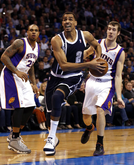 Oklahoma City Thunder's Thabo Sefolosha (2) splits defenders Shannon Brown (26) and Goran Dragic (1) as the Oklahoma City Thunder play the Phoenix Suns in NBA basketball at the Chesapeake Energy Arena in Oklahoma City, on Monday, Dec. 31, 2012.  Photo by Steve Sisney, The Oklahoman